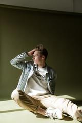 молодой человек  в светлой футболке позирует сидя  на бумажном фоне оливкового цвета в фотостудии