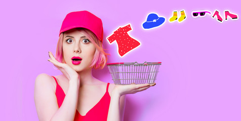 portrait of surprised young woman with shopping basket and clothes on the wonderful purple studio background