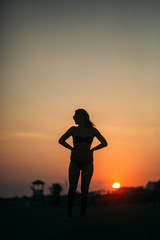 Beautiful girl sunbathing on a sandy beach. sunset silhouette