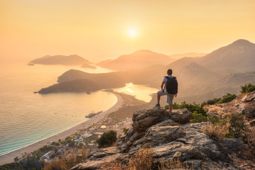 Young sporty man with backpack standing on the top of rock and looking at the seashore and mountains at sunset in summer. Scene with man, sea, mountain ridges and orange sky with sun. Oludeniz, Turkey