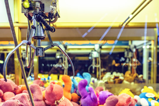 Night view to claw machine full of colorful soft toys