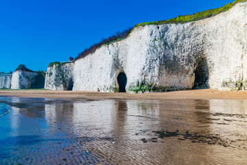 View of white chalk stacks and cliffs, sea at low tide and beach in Kingsgate Bay, Margate, East Kent, UK
