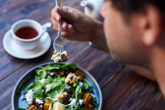 Man eating delicious salad while sitting at a bistro table