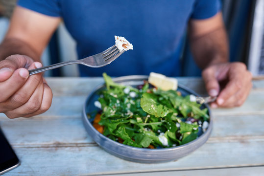 Man eating delicious salad at a rustic wooden table
