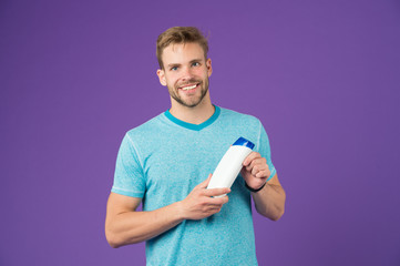 Happy man hold shampoo bottle on violet background. Bearded man smile with gel tube on purple background. Skincare and hair care. Health and healthcare. Cosmetic for spa and bath or shower