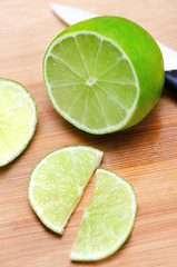 Juicy slice of lime on wooden cutting board