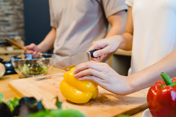 Woman hands cutting bell pepper in the kitchen. Beautiful happy asian couple are cooking in the kitchen. Young asian couple have romantic time while staying at home. Couple lifestyle at home concept.