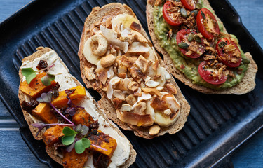 Toasted open faced sandwiches on a skillet and blue table
