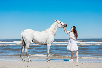 Young girl petting white horse on the beach.