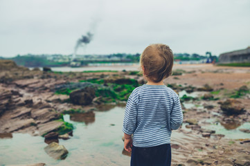 Little boy on beach watching fire in the distance