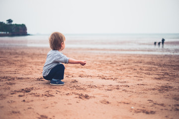 Little toddler boy sititng on beach