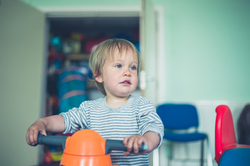 Cute little boy on tricycle indoors