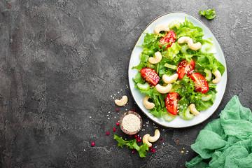 Salad with fresh vegetables and nuts. Vegetable salad with fresh vegetables and cashew. Vegetable salad on plate. Healthy vegetarian food
