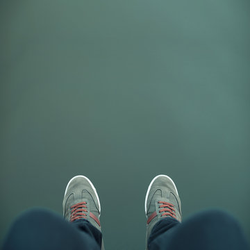 Minimal picture some legs with green sneakers over a green abyss, background, water, environment.