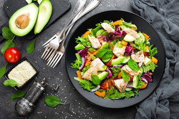 Salad with fish. Fresh vegetable salad with salmon fish fillet. Fish salad with salmon fillet and fresh vegetables on plate