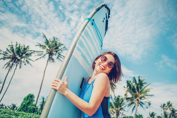 Smiling woman with surfboard posing on tropical beach