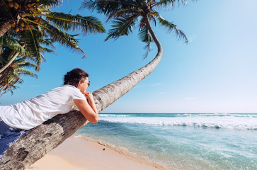 Woman lies on the palm tree and looks on ocaen waves. Summer vacation concept image