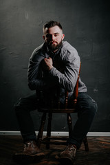 Brutal handsome man sitting on chair