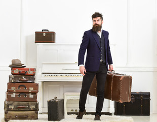 Luggage and vacation concept. Man, traveller with beard and mustache with luggage, luxury white interior background. Macho elegant on strict face stands near pile of vintage suitcase, holds suitcase.