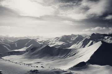 Fototapete - Black and white snowy mountains and sunlight off-piste slope