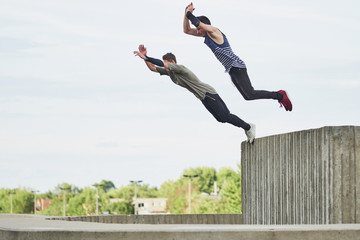 Teenage free runners jumping off concrete structure
