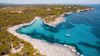 Aerial drone view of beautiful turquoise sea with rocky shore and green trees. White sailing boat in the middle of the bay. Island of Mallorca, Spain. Sunny summer day