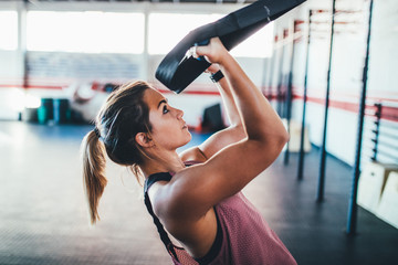 young adult trained woman concentrate at her excercise in gym