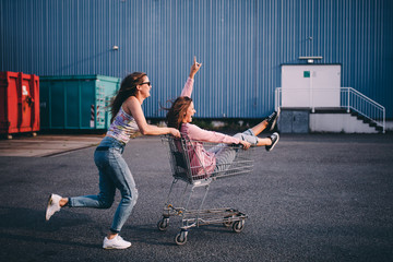 Young adult hipster friends having fun with shopping trolley