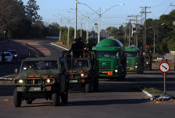 Army officers escort trucks transporting fuel on BR-116 highway in Canoas