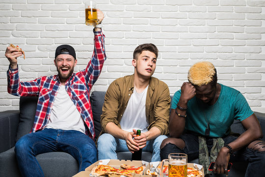 Three young mixed race men sitting on sofa drink beer and eat pizza support different team and with different emotion of lose and win at home