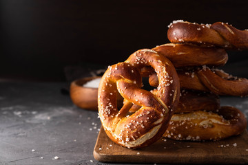 Freshly baked homemade soft pretzel with salt on rustic table. Perfect for Octoberfest.