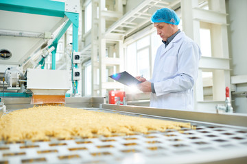 Side view portrait of senior factory worker  in food industry holding clipboard standing by conveyor belt, copy space