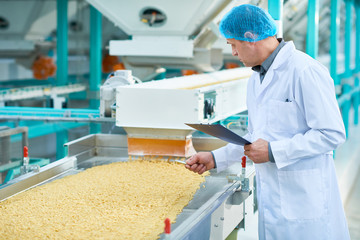 Side view portrait of senior factory worker doing  production quality inspection in food industry holding clipboard standing by conveyor belt, copy space