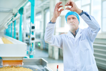 Waist up portrait of senior factory worker doing quality inspection in food industry holding two macaronis standing by conveyor belt, copy space