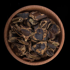 ground dried carob in wooden cup isolated on black. top view