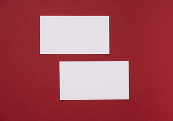 Two business cards on red background