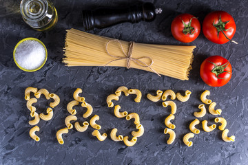 Uncooked pasta cavatappi and spaghetti with ingredients for tomato sauce. Concept of the composition of food design.