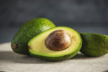 Avocado fruit cut in half on the linen fabric background. Concept organic eco products for food and cosmetic procedures