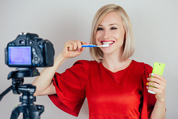 beautiful blond videoblogger ( beauty blogger ) woman in a red dress records video blog about the care of teeth on a video camera in a studio. concept of fresh breath and healthy oral cavity