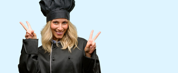 Beautiful cook woman chef looking at camera showing tong and making victory sign with fingers
