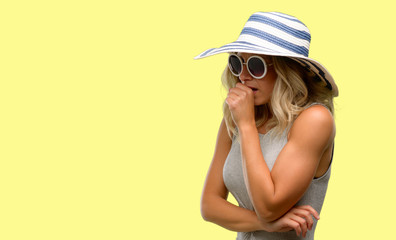 Young woman wearing sunglasses and summer hat sick and coughing, suffering asthma or bronchitis, medicine concept