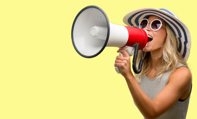 Young woman wearing sunglasses and summer hat communicates shouting loud holding a megaphone, expressing success and positive concept, idea for marketing or sales