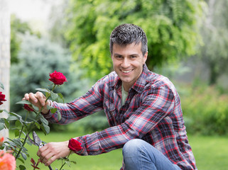 Gardener with scissors and red rose