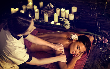 Massage of woman in spa salon. Girl on candles background treats problem back. Relaxation for...