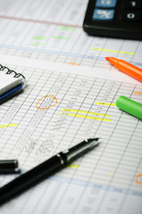 Financial calculations in a table on paper, pen, highlighter and calculator. Vertically