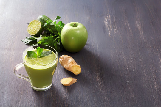 Fresh green smoothies with parsley, ginger, apple, lime and mint in a glass on a black wooden table with low back light. Healthy food. Copy space