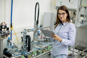 Young woman with digital tablet in the electronics workshop