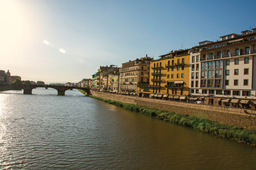 Overview of the river Arno, bridge and buildings at sunset. In the city of Florence, the famous and amazing capital of the Italian Renaissance. Located in the Tuscany region