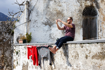 Tourist sits and taking photo near old italian building on Amalfi, Italy, Europe. man, hipster with beard and sunglasses