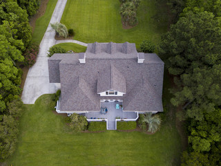 Aerial view of large home with new roof on beautiful property.